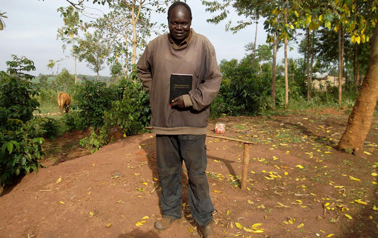 Picture of Maurice in East Africa holding his own Bible