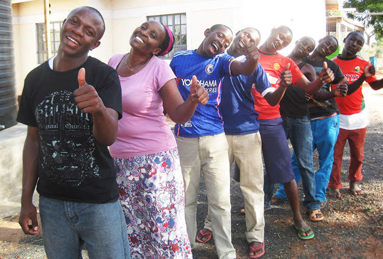 samuel and patricia giving thumbs up with men at Philemon house