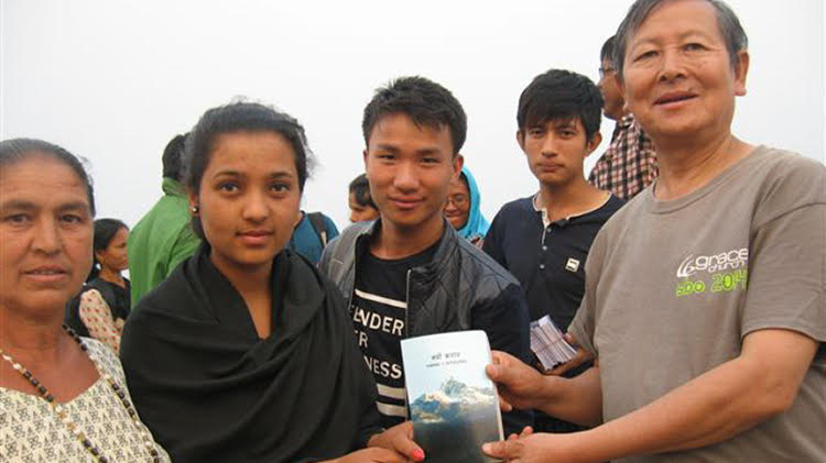 Nepali evangelist Timothy Rai giving away Bible