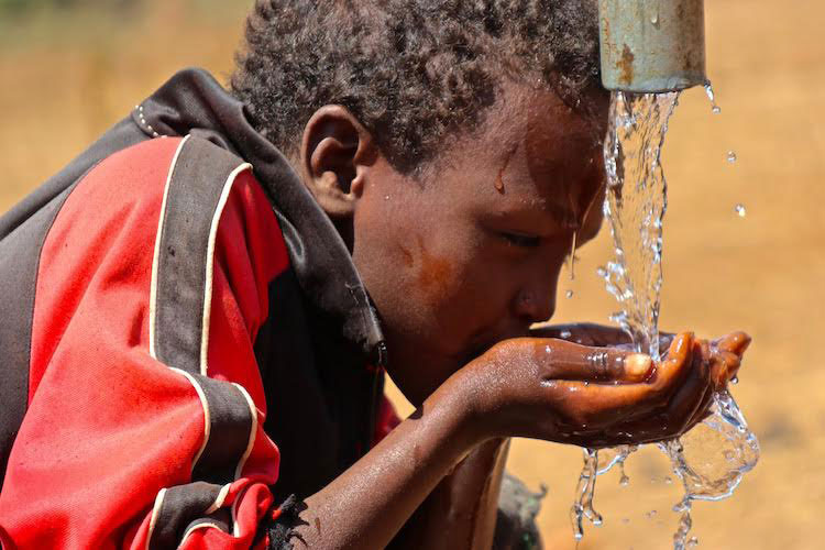 child drinking pure water from well in Ethiopia