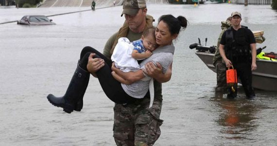 image of man carrying mother and baby, flood victims of hurricane harvey