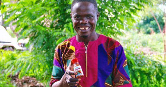 Robert, a borrower in Uganda, holding his chili powder product