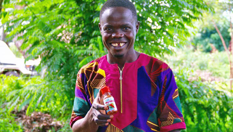 Robert, a borrower in Uganda, holding his chili powder product