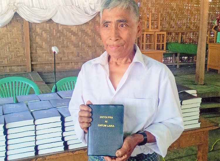 Man from Myanmar holding Bible he received from the Strategic Bibles Ministry