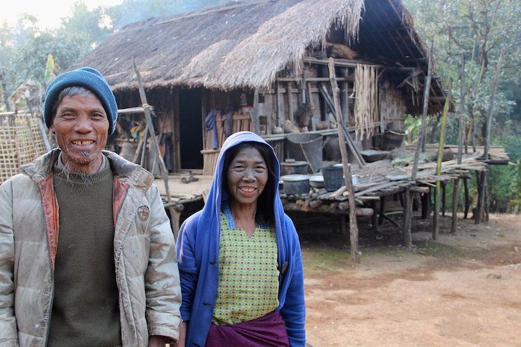 Poor couple in front of hut in chin state Myanmar