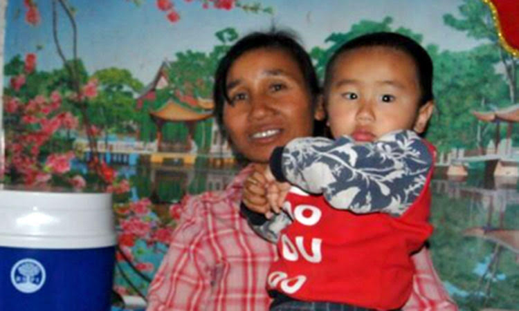 Sister Ai from unreached people group in China holding grandson