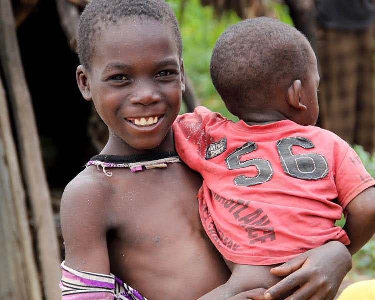 Child in poverty holding little brother and smiling