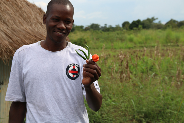 Picture of man with plant, able to farm thanks to the Microloan Ministry