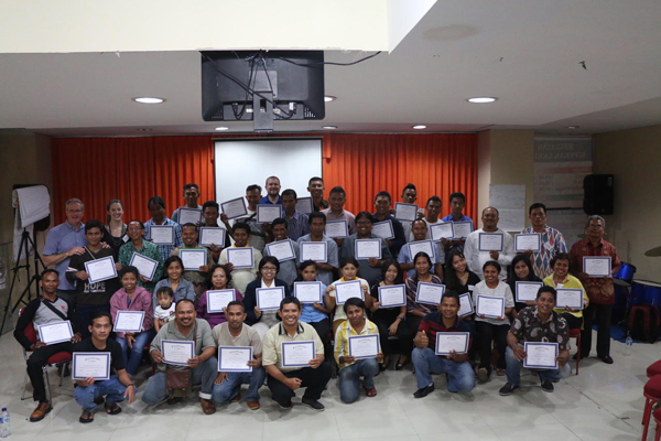 Picture of a group of micro-bankers/borrowers holding certificates after completing training