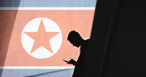 Man holding phone against North Korean flag