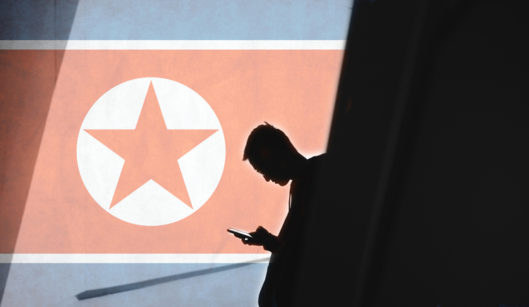 Man holding phone against North Korean flag