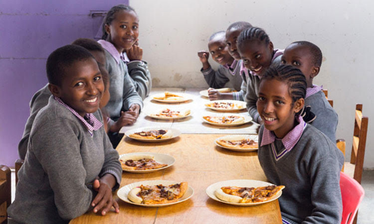 Picture of girls in Kenya enjoying pizza