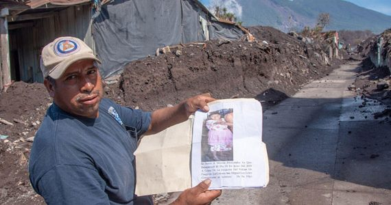 Picture of man in Guatemala and volcano Fuego smoking in distance