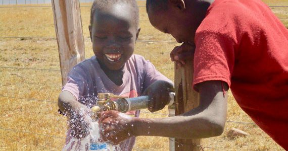 Child in Africa enjoying safe drinking water