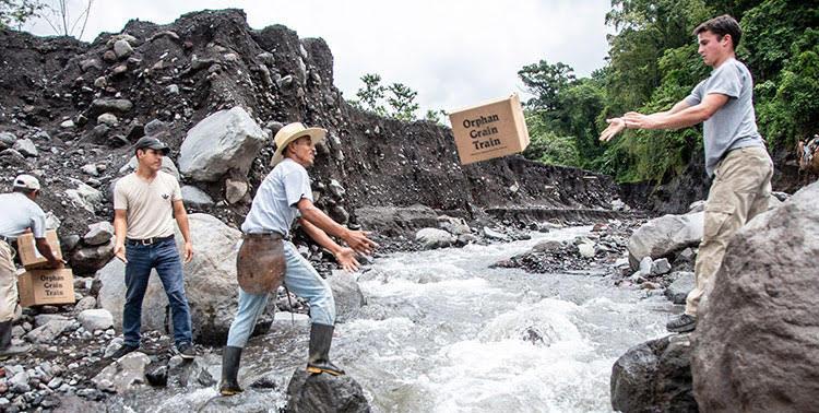 Picture of relif team throwing emergency supplies across river in Guatemala