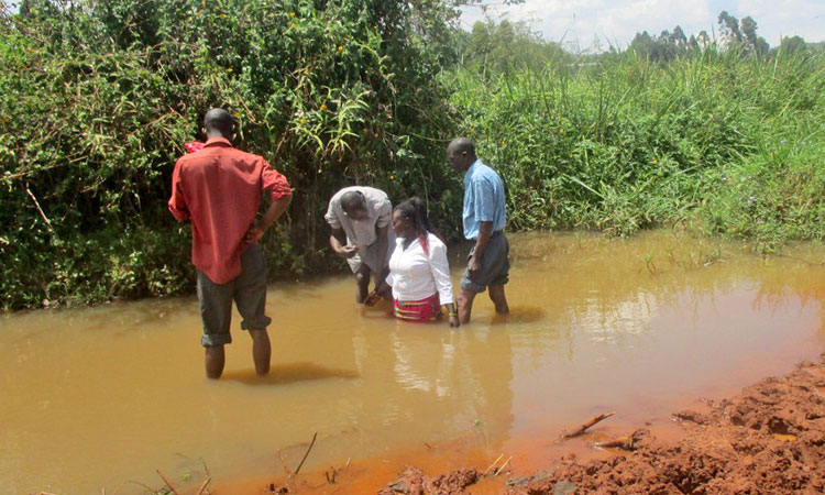 Picture of woman in Kenya being baptized in muddy water