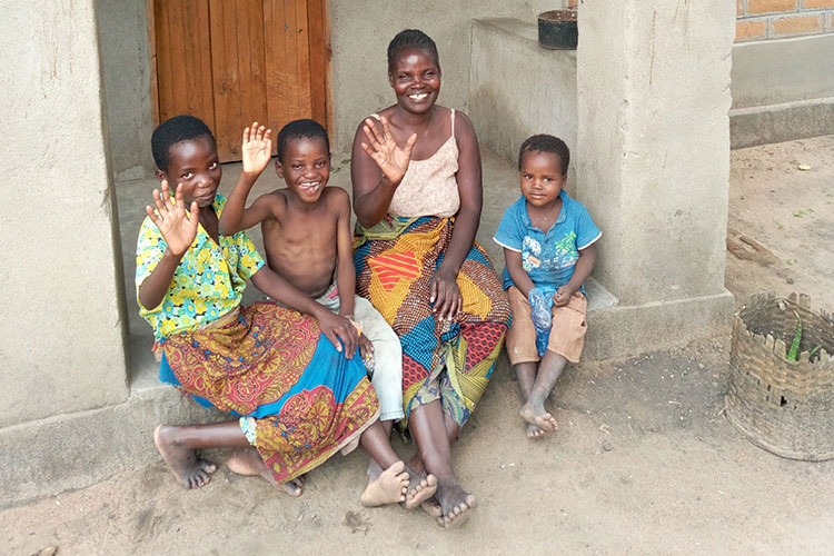 Picture of family in Malawi with house provided by Disaster Relief Ministry