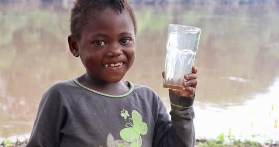 Picture of girl in Cameroon holding glass of safe water