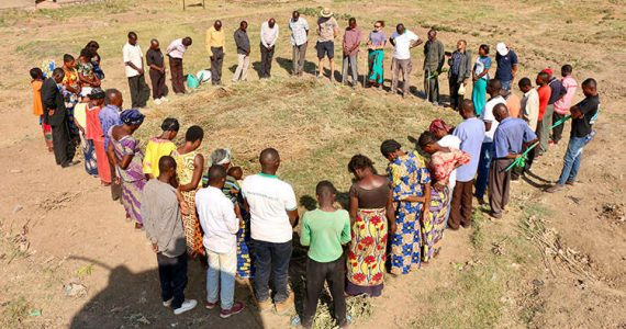 Picture of farmers praying over farmland