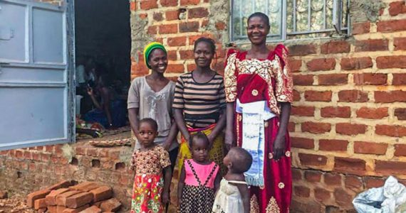 Picture of Christine, a former victim of sexual violence in DR Congo, with her family in front of their finished house