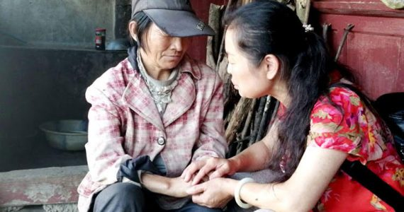 Picture of missionary praying with unreached person in China